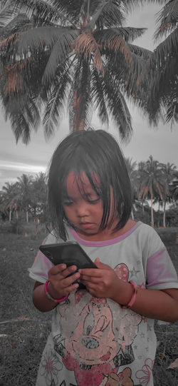 Low angle view of girl using mobile phone against trees