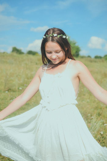 Teenage girl holding white dress while standing on field during sunny day