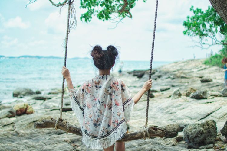 Rear view of woman on swing by sea against sky