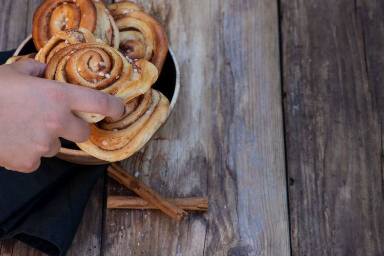 A Hand grabs kanelbullar Kanelbullar Adult Cinamonrolls Close-up Coffeeshop Coffeetime Day Finger Food Food And Drink Fresh Freshness Hand High Angle View Holding Human Body Part Human Hand Indoors  Lifestyles One Person Real People Table Unrecognizable Person Vegetable Wood - Material