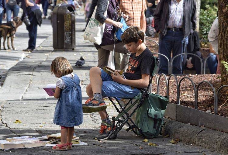 Children Girl Boy Full Length Sitting Standing Reading Books Reading A Book Outdoors Day Real People Street Photography The Week On EyeEm Piazza Santo Spirito Visit Italy Florence Lifestyles Life Is Art People Relaxing Studying Read A Book Reading Time Learning To Read