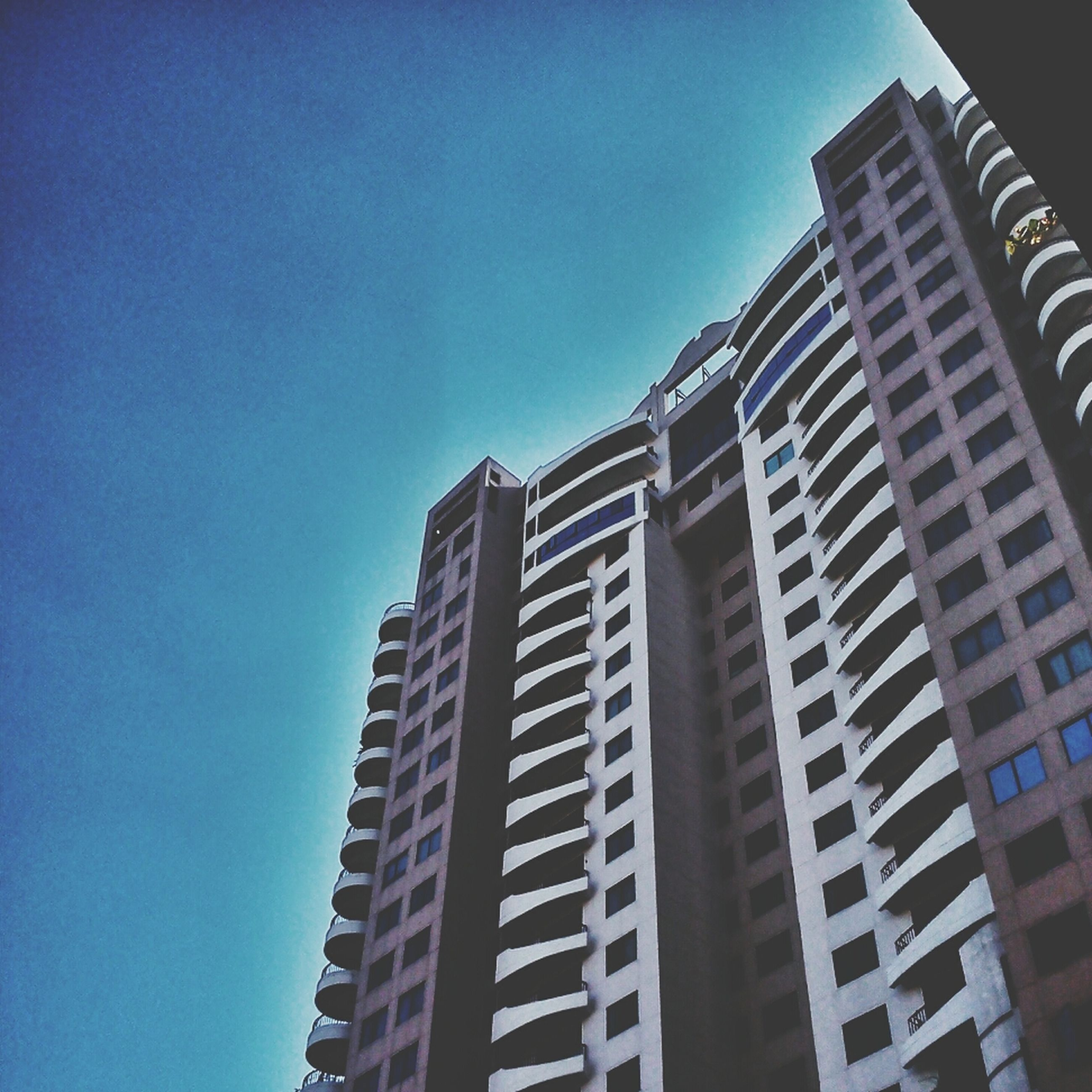 building exterior, architecture, built structure, low angle view, clear sky, city, blue, building, office building, modern, skyscraper, tall - high, tower, residential building, sky, copy space, residential structure, window, outdoors, day