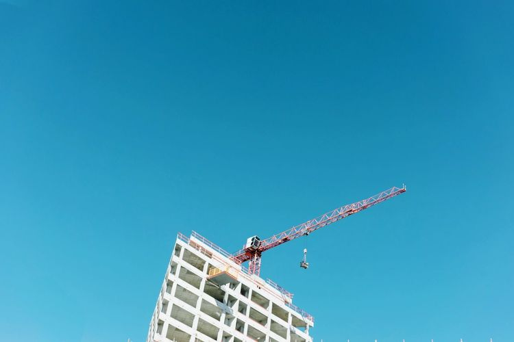 Low angle view of crane by building against clear blue sky