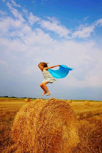 Girl jumping over hay bale on field against sky
