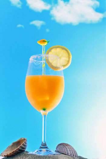 Close-up of drink on table against blue sky