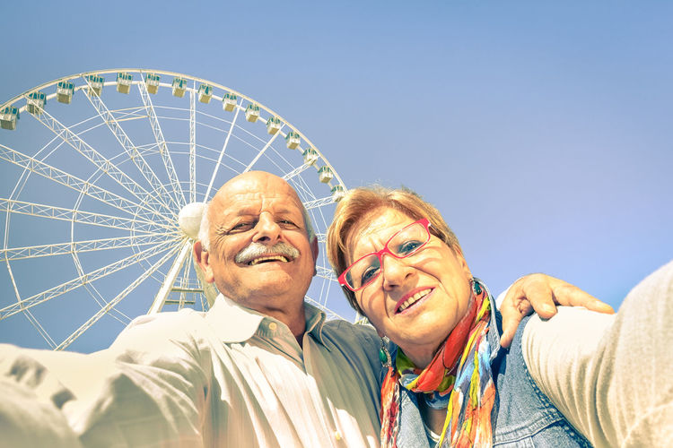 Low angle view of senior couple against ferris wheel