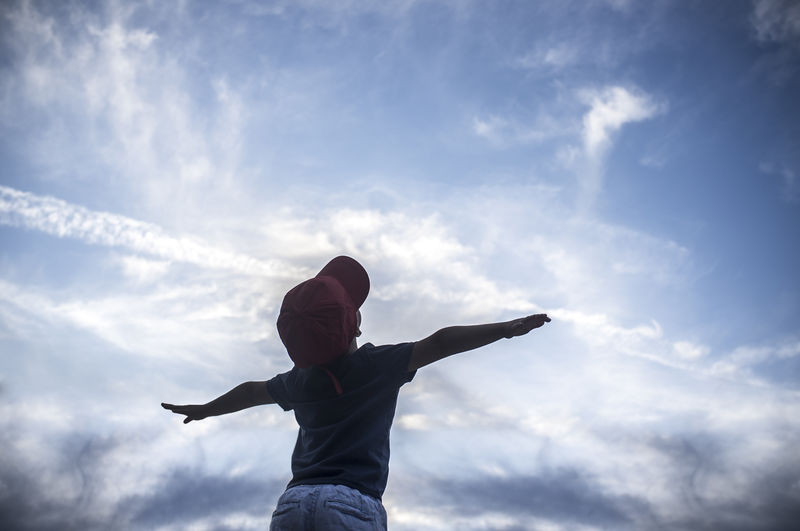 Low angle view of boy with arms outstretched standing against sky