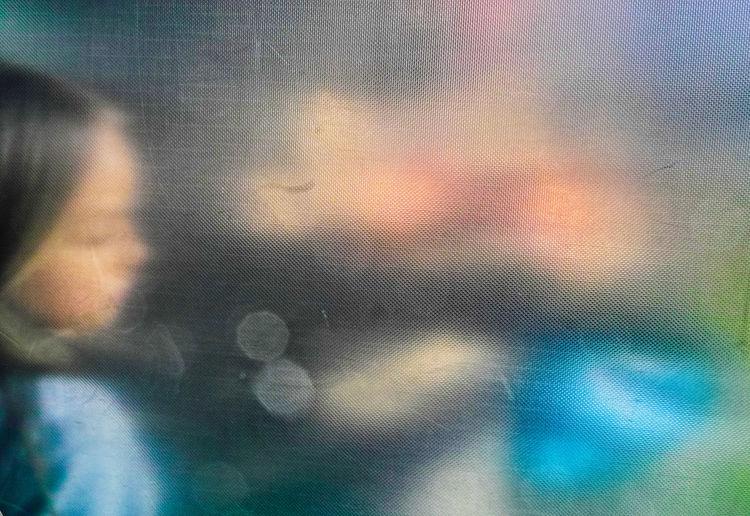 Defocused image of person seen through wet glass window