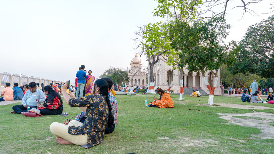 Group of people sitting on grassland against the sky