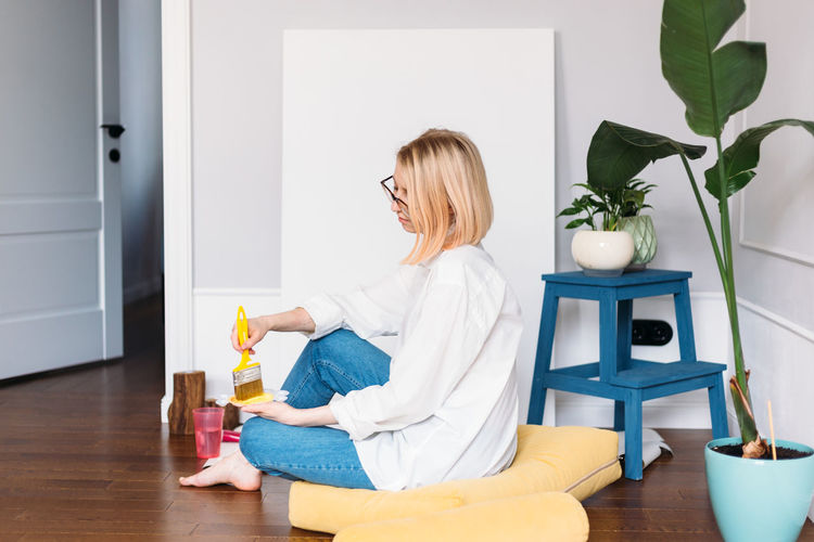 Woman sitting on floor at home