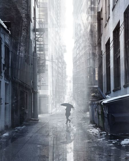 Man With Umbrella Walking On Street Amidst Buildings In City During Rainy Season