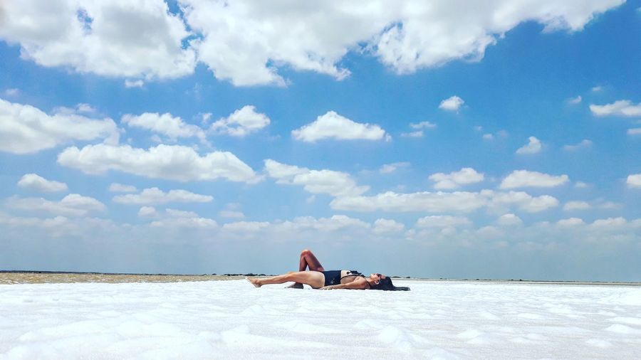 Man lying on shore against sky