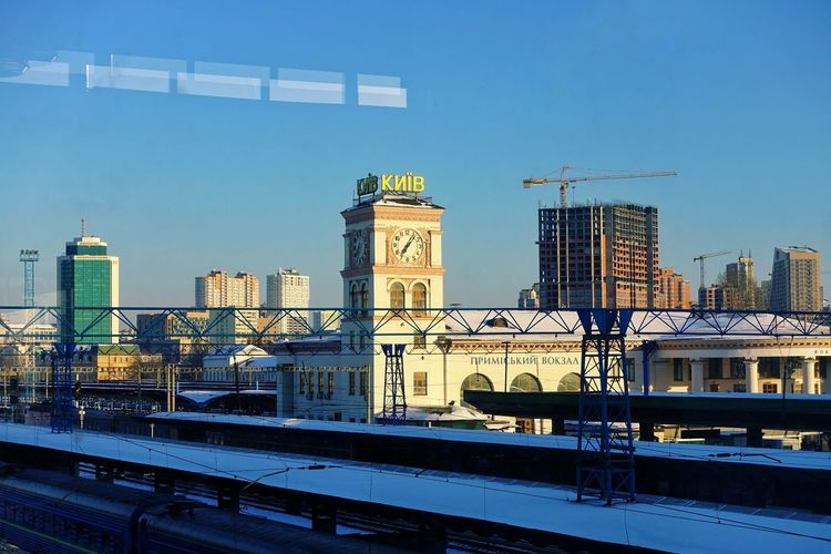 Kyiv-Pasazhyrskyi railway station, Kyiv, Ukraine. Transportation Outdoors Kyiv Kyiv,Ukraine Ukraine Ukraine 💙💛 Railroad Station Built Structure Architecture Building Exterior Rail Transportation No People Snow Cold Temperature Winter Springtime Top View Top Perspective Reflection Through The Window City Building Clear Sky Clock Tower Capital City Railing Connection Blue Sky Industry