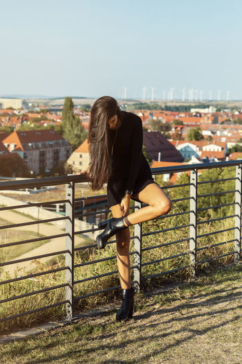 Rear view of woman standing on railing against cityscape