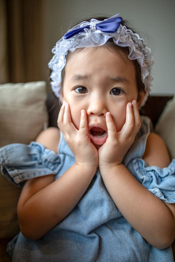 Surprised!!! Child Childhood Cute Emotion Front View Furniture Girls Happiness Home Interior Indoors  Innocence Lifestyles Looking At Camera Mouth Open One Person Portrait Real People Sitting Sofa
