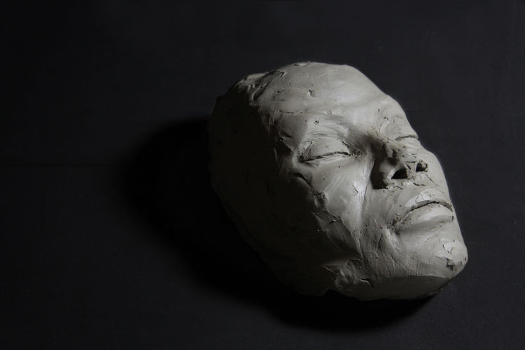 Clay sculpture, with closed eyes. face whit shadows, liyng on black floor.