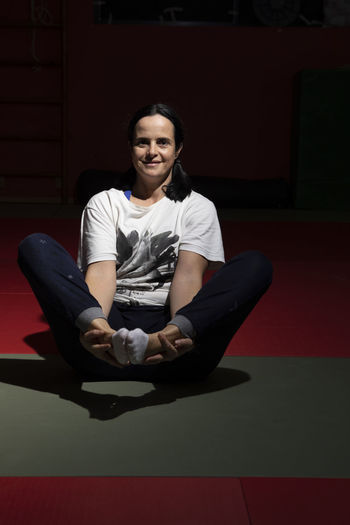 Portugal; Aula de Yoga Yogagirl Yoga Poses Sitting One Person Looking At Camera Full Length Front View Real People Casual Clothing Portrait Indoors  Leisure Activity Young Adult Lifestyles Smiling Red Relaxation Cross-legged Wireless Technology Women Beautiful Woman Hairstyle