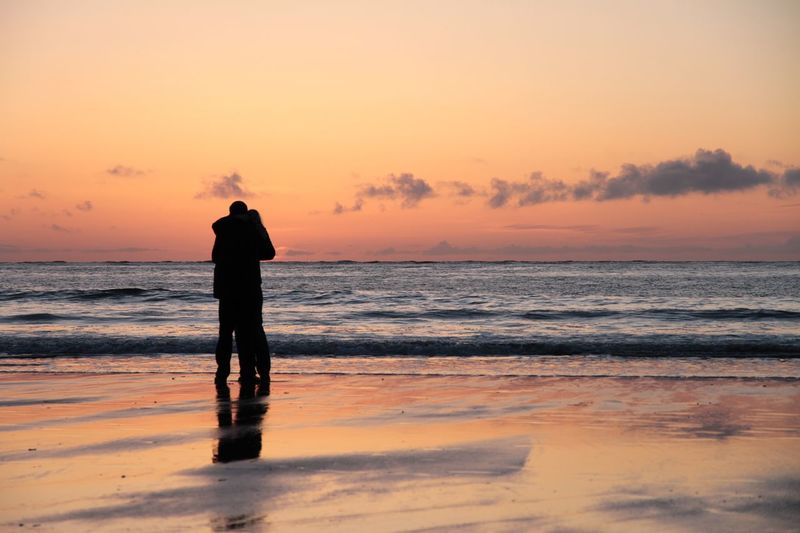 Couple On Beach Against Sunset Sky