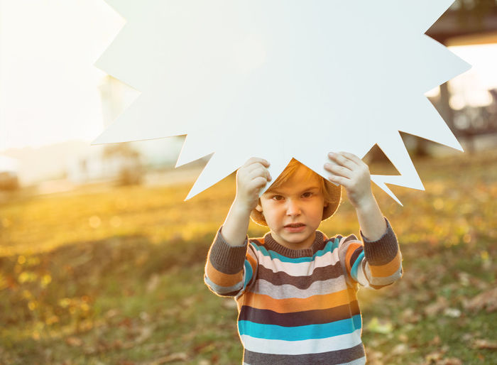 Close-up of boy standing on paper