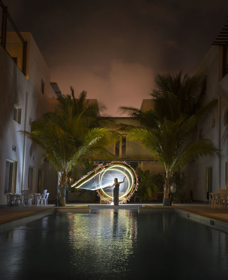 Scenic view of swimming pool by building against sky at night