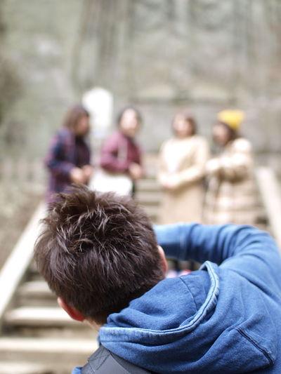 Rear View Of Man Wearing Blue Hooded Shirt Bending Outdoors