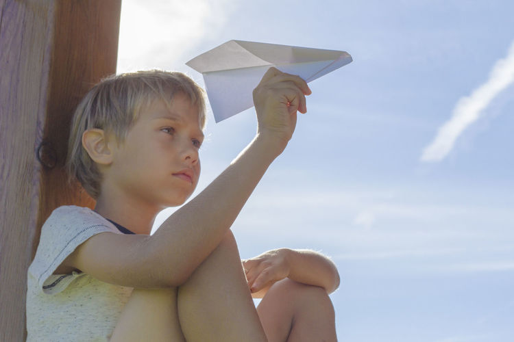 Boy holding paper airplane against cloudy sky