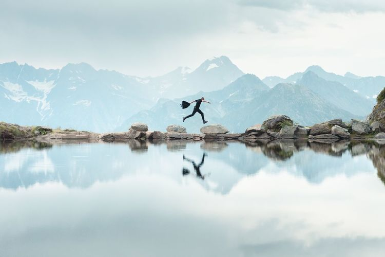 Man Reflecting On Calm Lake While Jumping Mountains Against Cloudy Sky