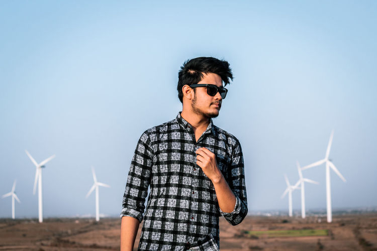 Renewable Energy Environment Environmental Conservation Alternative Energy Fuel And Power Generation Wind Turbine Turbine Sky Young Adult One Person Wind Power Young Men Nature Glasses Standing Technology Clear Sky Sunglasses Blue Land Fashion Wind Sustainable Resources