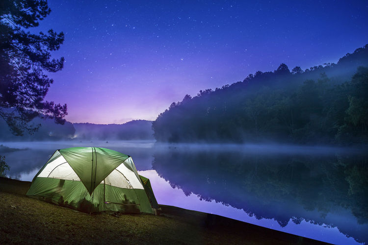 Tent by lake against sky at night