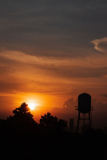 Silhouette water tower against sky during sunset