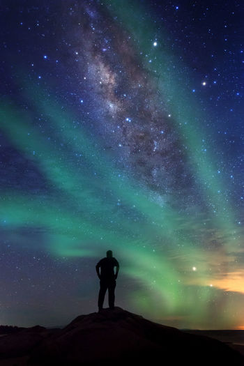 Rear view of silhouette man standing against star field at night