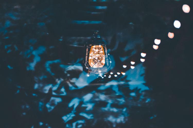Low angle view of illuminated lantern indoors