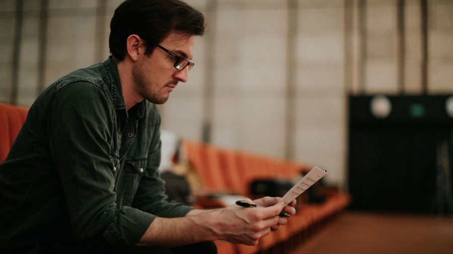 Side view of young man using mobile phone at home