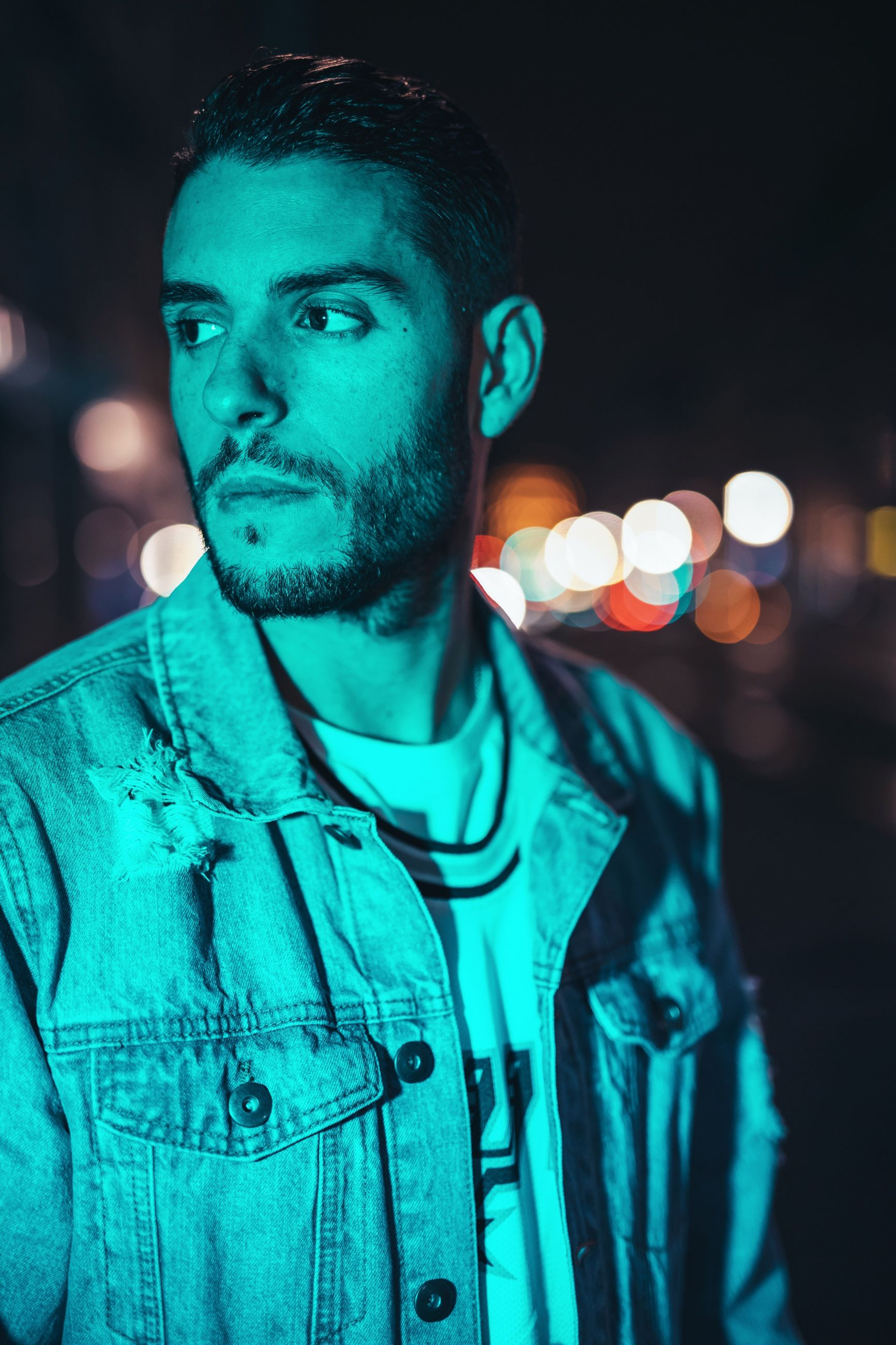 illuminated, night, real people, one person, green color, front view, outdoors, lifestyles, young adult, portrait, close-up, people