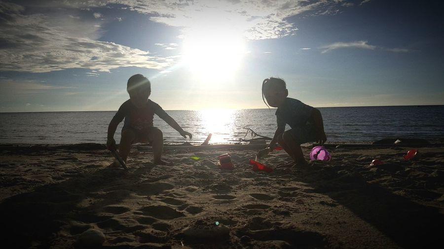 Silhouette men sitting on beach against sky during sunset