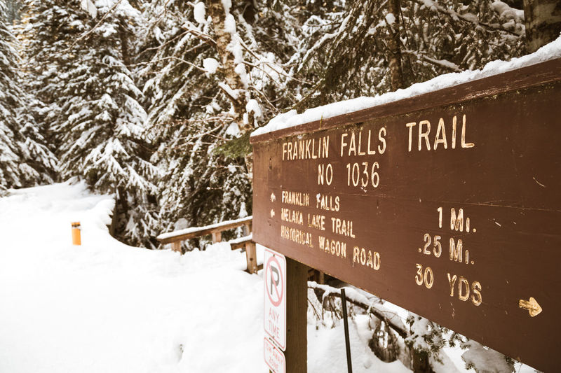 A trail sign for Franklin Falls in Washington in the depth of winter, deep in snow. Snoqualmie. Franklin Falls Snoqualmie Trail Trail Sign Washington Winter Snow Cold Temperature Tree Sign Nature Information No People Information Sign Guidance Outdoors Day Directional Sign Directions Deep Snow Winter Wintertime Hiking