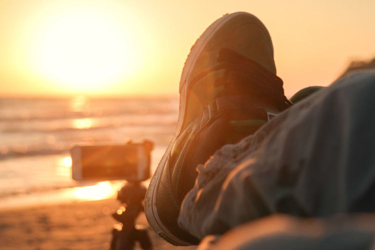 Close-up of shoe by sea during sunset