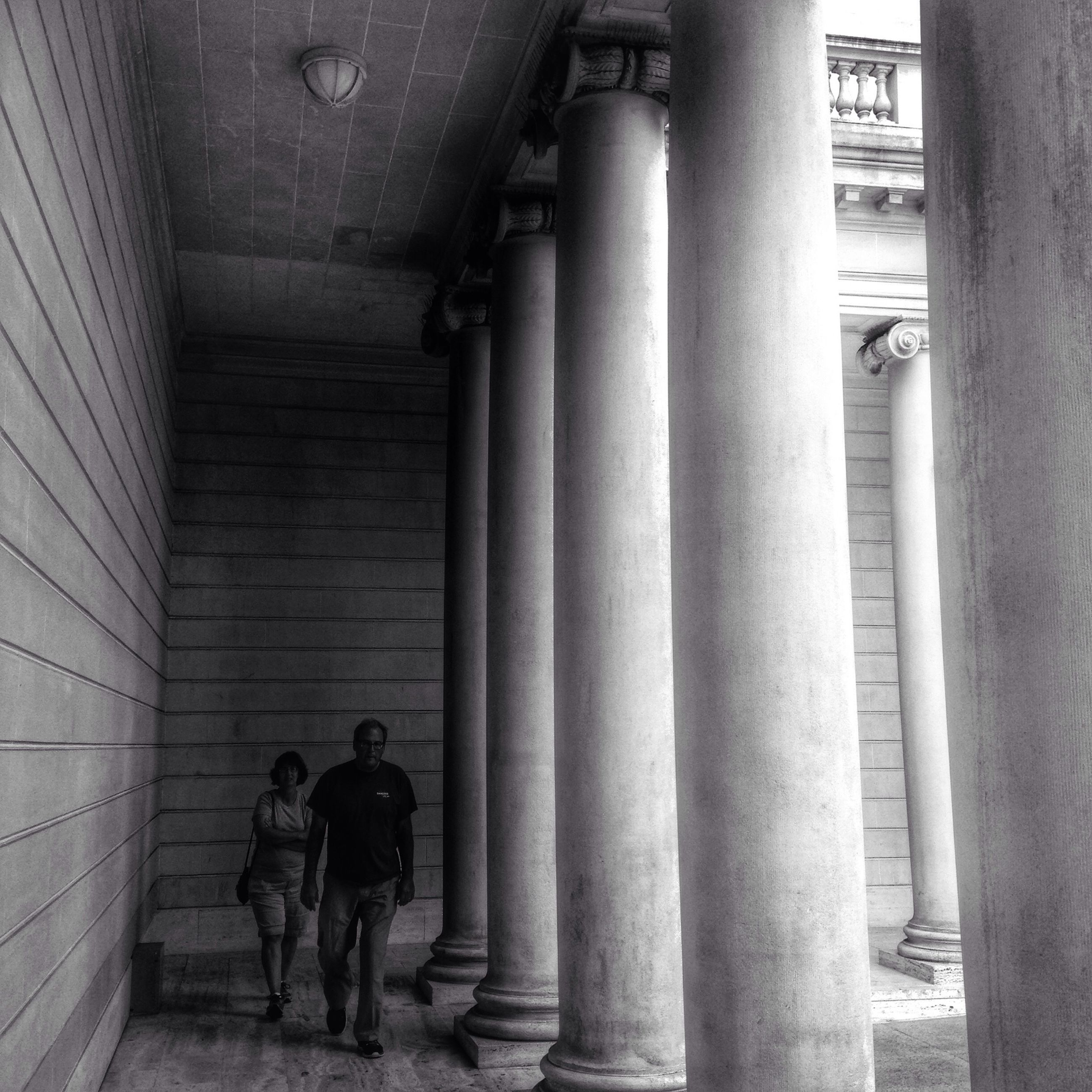 indoors, lifestyles, men, architecture, built structure, leisure activity, full length, rear view, person, architectural column, walking, history, standing, steps, column, corridor, togetherness