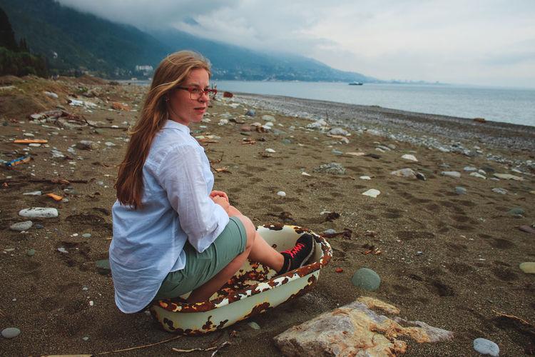 Woman sitting on abandoned bathtub at sandy beach