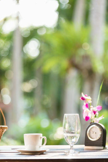 Beauty In Nature Coffee Coffee Cup Day Drink Flower Flower Head Focus On Foreground Food And Drink Glass Nature No People Outdoors Table Tea Cup
