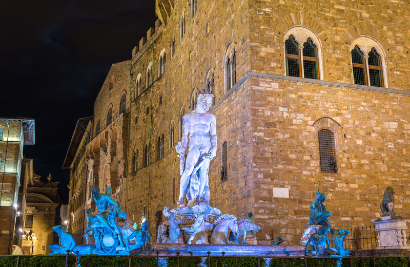 Low angle view of statue against historic building at night