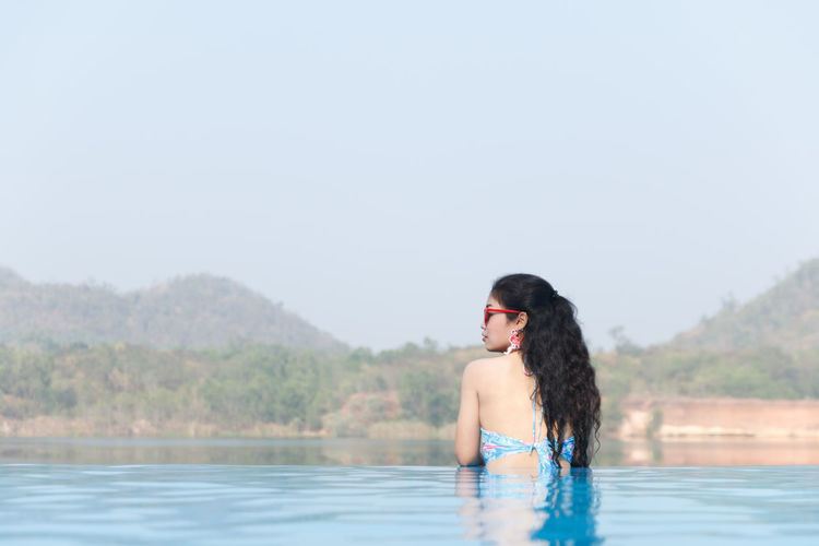 Young woman in infinity pool against clear sky