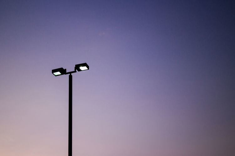 Silhouette Of Illuminated Floodlight Against Sky