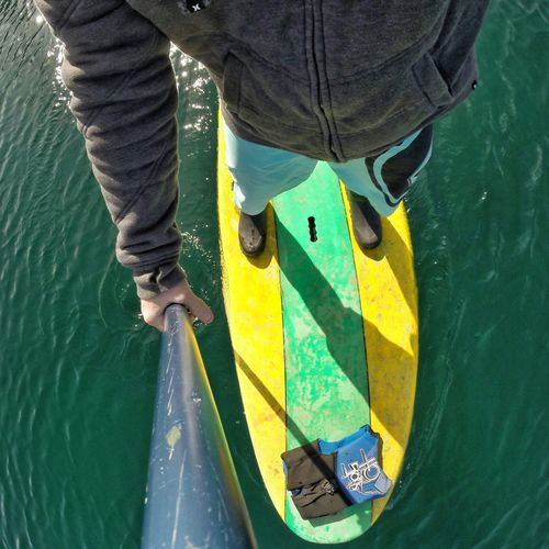 Directly below shot of man paddleboarding in sea