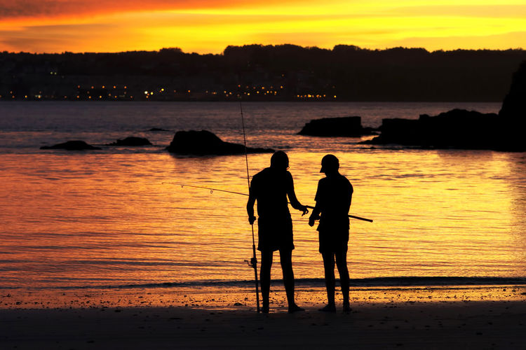 Silhouette of men fishing on beach at sunset