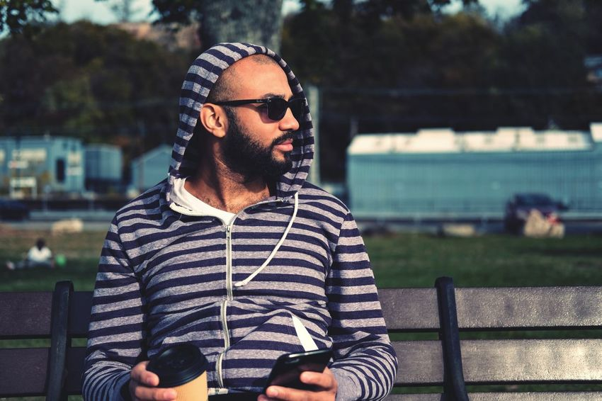 One Man Only Sitting One Person Adults Only Casual Clothing Outdoors Focus On Foreground Beard Grass Young Adult Day Shades Wireless Technology Leisure Activity Technology Only Men Adult People One Young Man Only Water Sky The Portraitist - 2018 EyeEm Awards