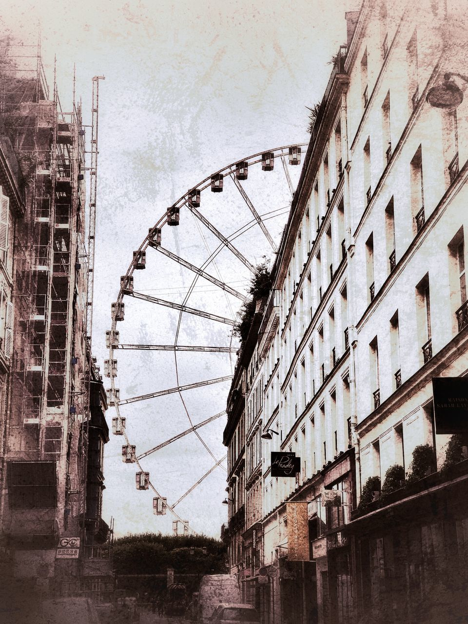 LOW ANGLE VIEW OF FERRIS WHEEL AGAINST BUILDING IN CITY