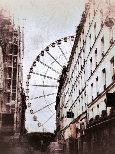 Low angle view of ferris wheel against buildings