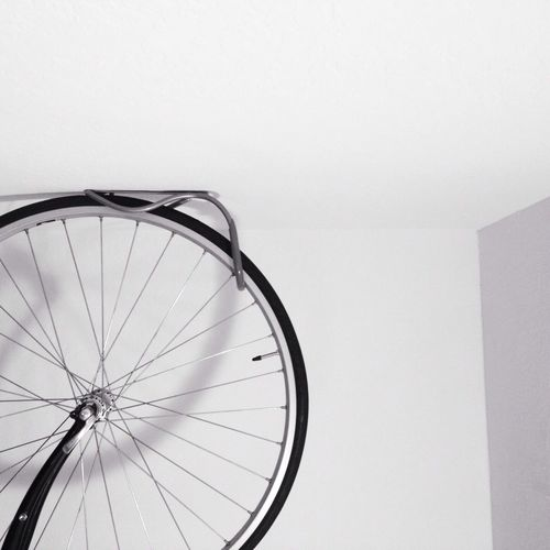 Close-up of cropped cycle wheel against white wall