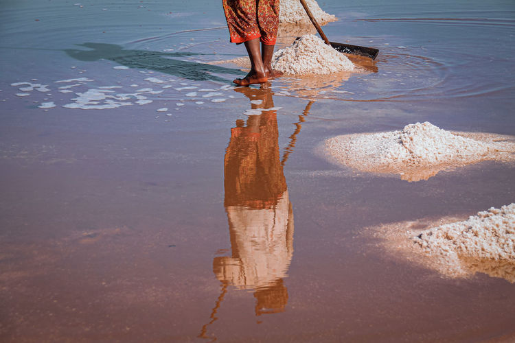 Low section of woman working whiel standing at salt flat